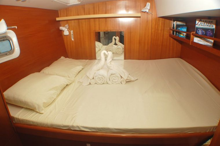 MIMBAW Yacht Charter - Port forward Stateroom Queen Bed.  All rooms have 2 fans and a hatch to catch natural ocean breezes.