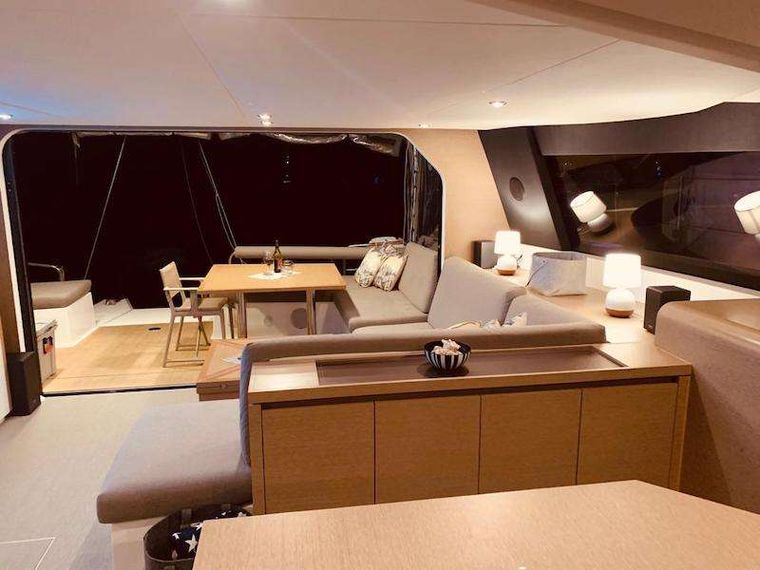 LA LINEA Yacht Charter - Outdoor - a pair of couches covered by a hard bimini - outdoor galley with fridge, grill and sink and a teak table with seating for 8.